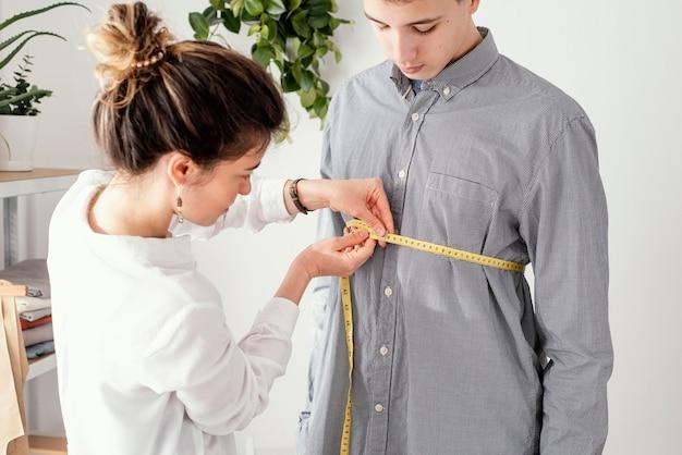 男性のクライアントのシャツを測定する女性の仕立て屋