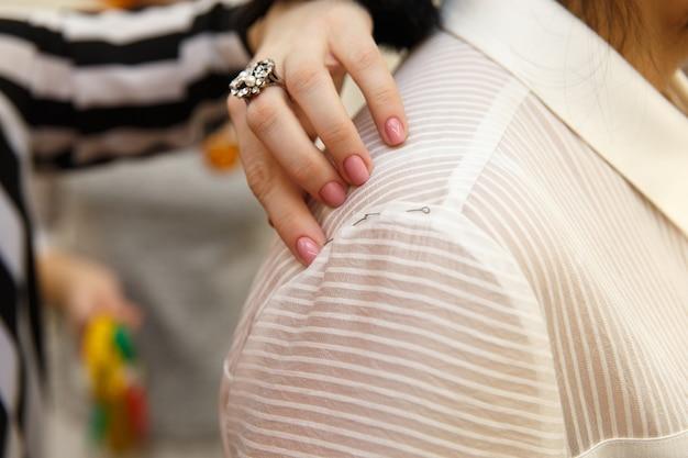Женский портной измеряет женское плечо, чтобы сшить костюм для красивой клиентки в ее портнихе