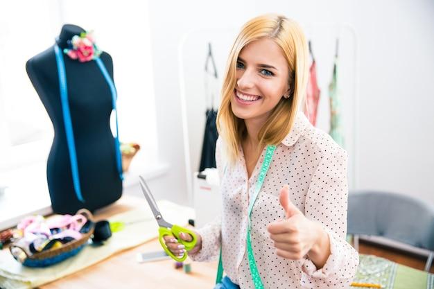 엄지 손가락을 보여주는 여성 재단사