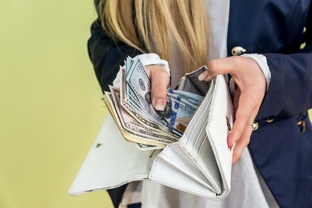 Женщина достает доллар из бумажника