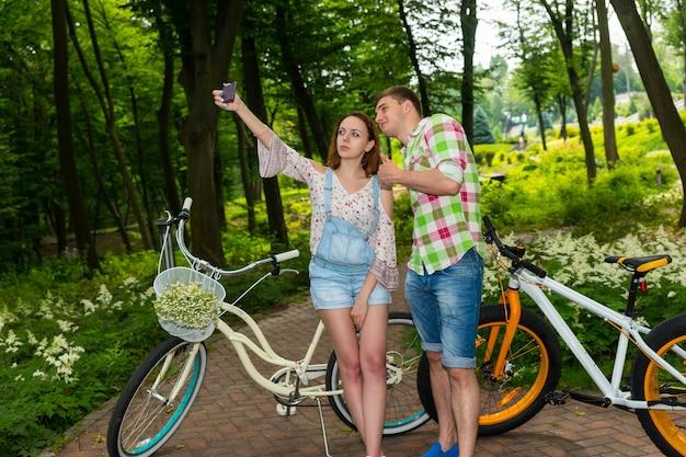 公園のバスケットに小さな白い花の花束を持って自転車に寄りかかって男と一緒に自分撮りをしている女性
