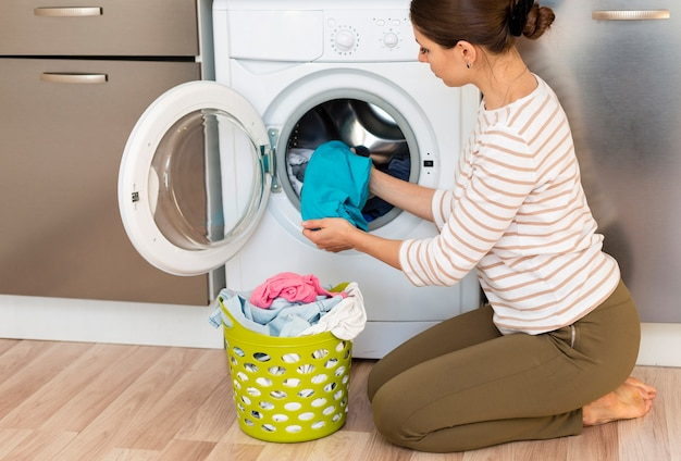Female taking clothes out washing machine