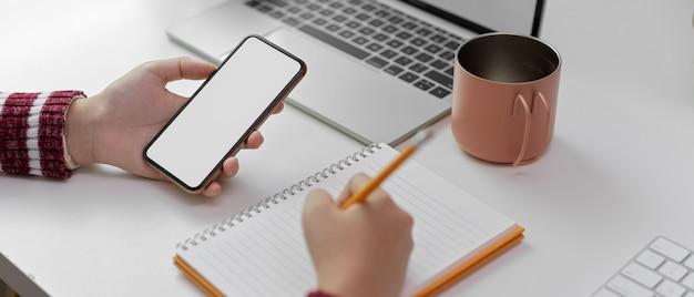 Женщина принимает к сведению пустой блокнот при использовании макета смартфона на белом рабочем месте