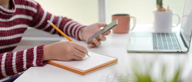 Женщина принимает к сведению пустой блокнот при использовании смартфона на офисном столе