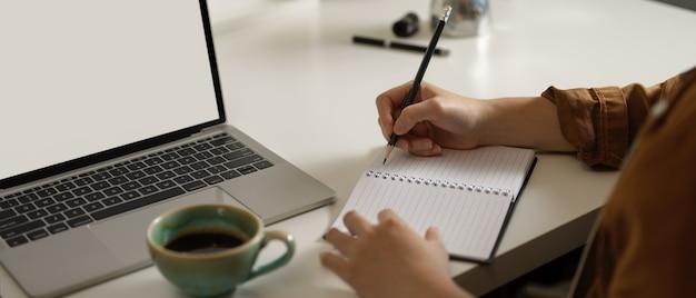 白いテーブルの上のノートパソコンのモックアップでの作業中に空白のノートブックにメモを取る女性