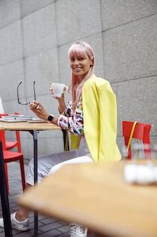 眼鏡を外し、コーヒーとカメラに笑顔の女性
