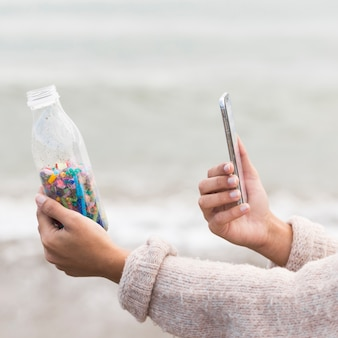 Female taking photo of bottle with plastic