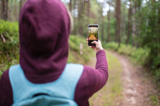 Женщина принимая фото лесного пейзажа с смартфон в руке