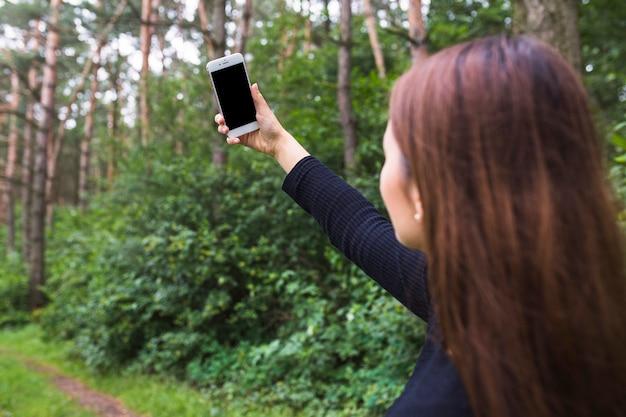 女性、森林の携帯電話でセルフを取っている