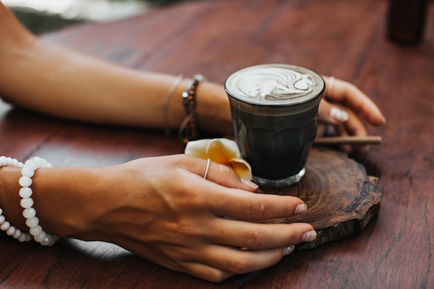 Female tanned hands holds glass of coffee with coconut milk