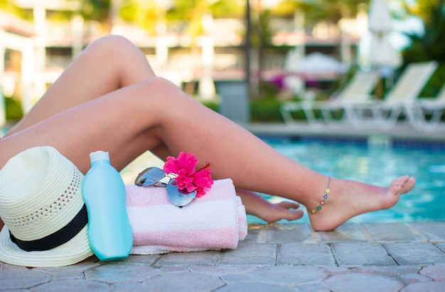Female tanned legs near sun cream, hat, towel and sunglasses against the swimming pool