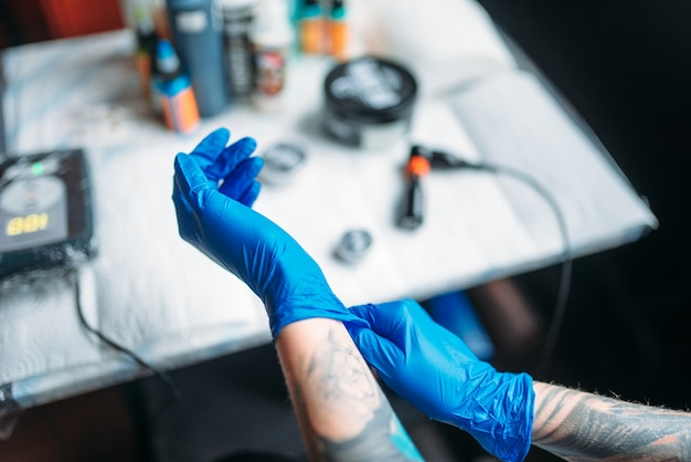 Female tattoo artist hands in blue sterile gloves, professional work tools. tattooing in salon