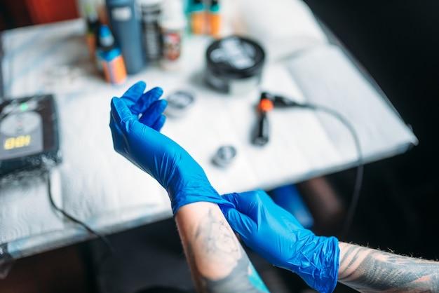 Женский татуировщик руки в синих стерильных перчатках, профессиональных рабочих инструментах. татуировка в салоне