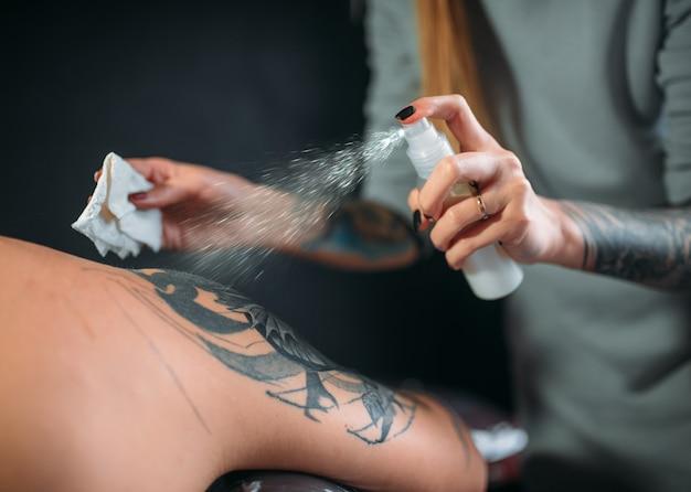 Женский мастер татуировки распыляет заморозку на коже клиентов, профессиональные инструменты. татуировка в салоне