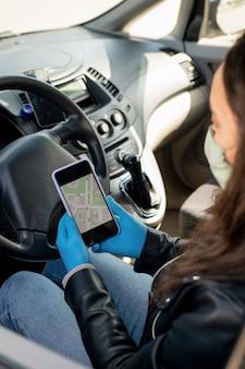 Женщина-водитель такси в защитных перчатках смотрит на карту навигатора в смартфоне, чтобы найти место проживания