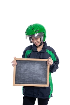 白い背景の上に分離された空白の黒板を保持しているヘルメットを身に着けている女性のタクシーバイクライダー