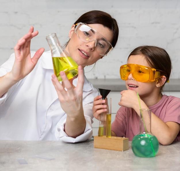 Учительница и девочка делают научные эксперименты с пробирками