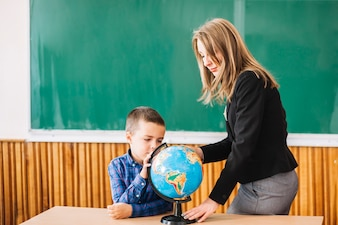 Female teacher and student boy working with globe