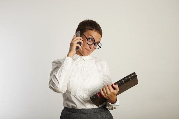 Female teacher in conservative outfit and round black glasses looks playfully while talking on the phone on white wall