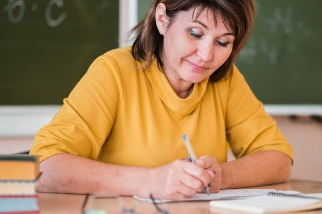 Female teacher at desk taking notes