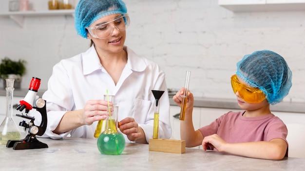 Insegnante femminile e ragazza con retine per capelli facendo esperimenti scientifici con il microscopio