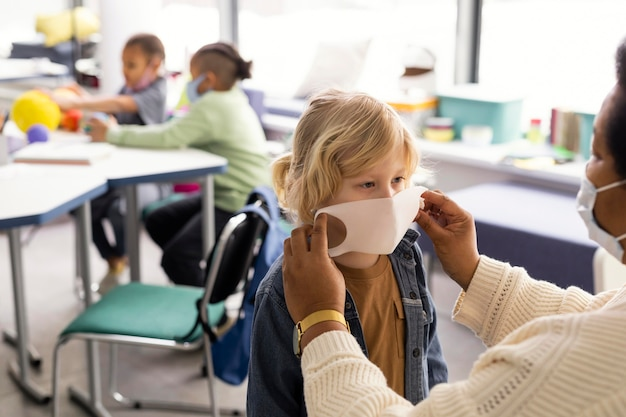Insegnante femminile che aiuta i bambini con la loro mascherina medica