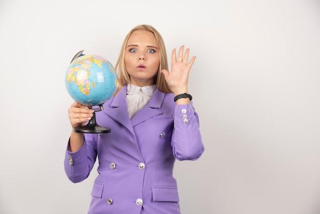 白い背景の上の地球を保持している女教師。高品質の写真