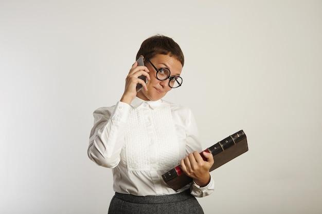 보수적 인 복장과 둥근 검은 색 안경을 입은 여성 교사는 흰 벽에 전화로 이야기하면서 장난스럽게 보입니다.