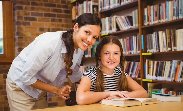 Female teacher and little girl in library
