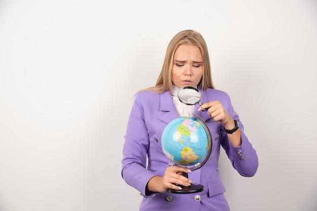 虫眼鏡で地球を見ている女教師。