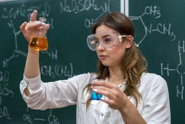 Учительница, проводящая эксперимент с жидкостью в колбе на уроке. наука интересна и увлекательна