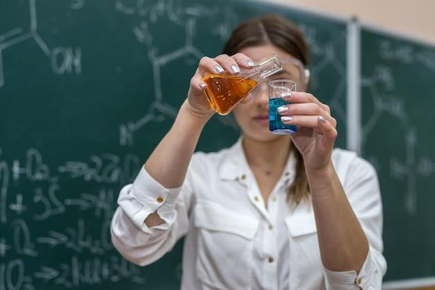 Учительница проводит эксперимент с жидкостью в колбе на уроке. наука интересна и увлекательна