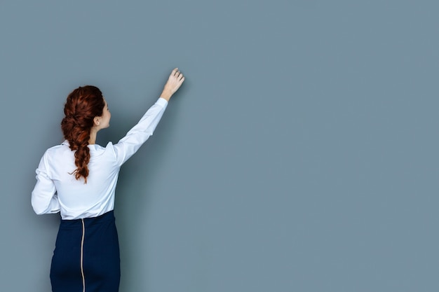 女教師。壁を書きながら立って見ている楽しいスマートな若い女性