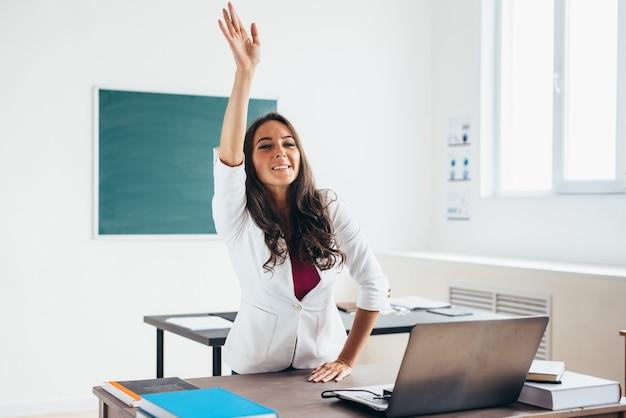 Female teacher raises hand sitting at the desk like a pupil.