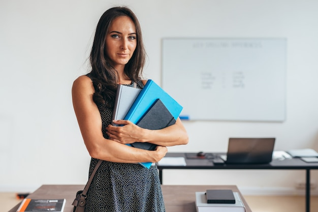 Female teacher smiling and posing in classroom