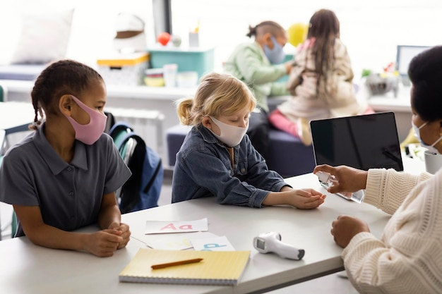 Female teacher teaching kids about disinfecting