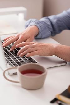 Учительница использует ноутбук, чтобы писать во время онлайн-класса и пьет чай