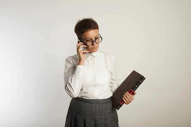 Female teacher in white blouse and grey tweed skirt holds an old book and talks on the phone on white