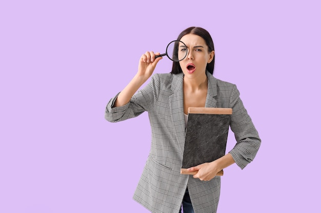 Female teacher with chalkboard and magnifier on purple