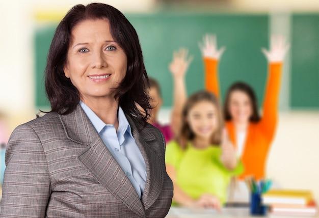 バックグラウンドでクラスで子供を持つ女教師