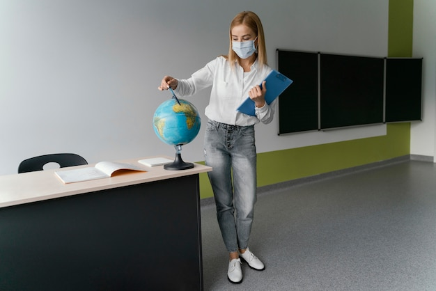 Female teacher with clipboard pointing to globe in classroom