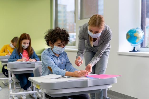 교실에서 아이들에게 손 소독제를주는 의료 마스크가있는 여성 교사