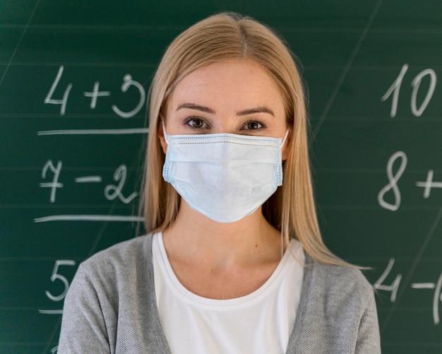 黒板の前の教室でポーズをとって医療マスクを持つ女教師