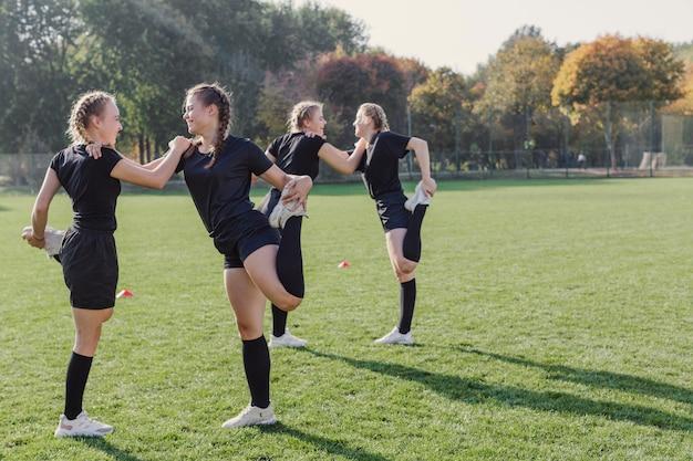 Female team doing warming up exercises