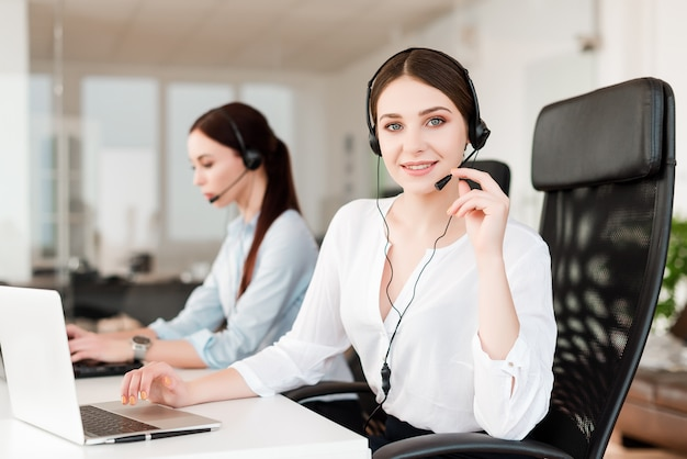 Female tech support agent with headset answering business calls in company office
