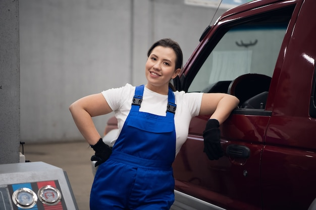 A female techie in blue overalls is standing at the car