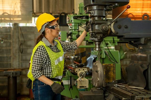 ヘルメットと制服を着た女性技術者が工場の機械を制御しています。