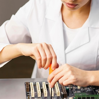 Female technician with electronics and tool