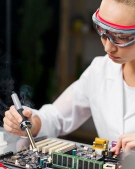 납땜 인두 및 전자 보드와 여성 기술자