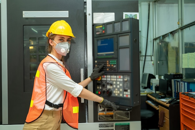 Female technician worker working and checking machine in a large industrial factory